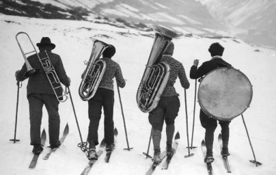 Athletes and the Arts - What we do - Traveling musicians - 4 musicians on skis in the mountains carrying trombone, euphonium, tuba, and bass drum
